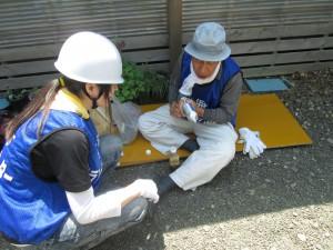 大工さんから工具の使い方を教えてもらう学生ボランティア